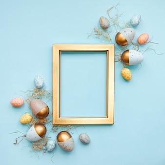 Vista dall'alto di uova di pasqua colorate con vernice dorata e colori diversi. sfondo blu. copia spazio.