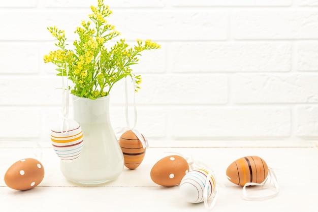 Vista dall'alto di uova di pasqua su fondo in legno decorato con fiori solidago in vaso bianco. uova di pasqua a strisce e punteggiate su un tavolo.