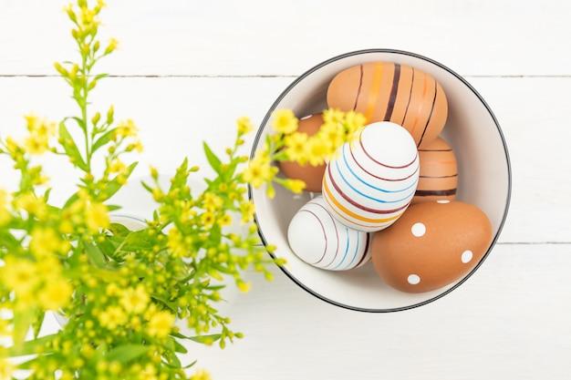 Vista dall'alto di uova di pasqua in una ciotola su fondo in legno decorato con fiori di solidago. uova di pasqua a strisce e punteggiate su un tavolo.