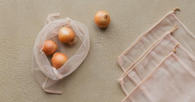 Vista dall'alto della borsa ecologica con coulisse con cipolle. acquista senza danni alla natura in sacchetti anti-plastica. confezioni ecologiche. zero rifiuti.