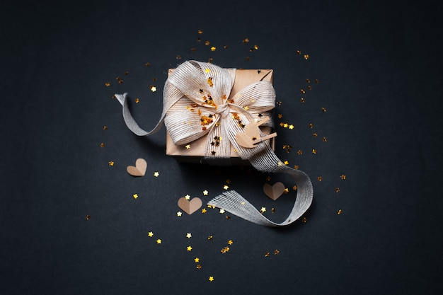 Vista dall'alto della confezione regalo eco decorata con stelle dorate e carte a forma di cuori, sulla superficie di colore nero