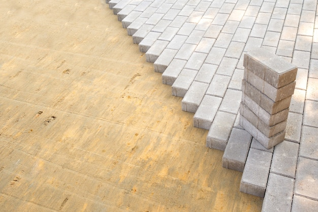 Vista dall'alto del bordo della superficie con lastre di pavimentazione grigie posate e superficie con impasto sabbioso