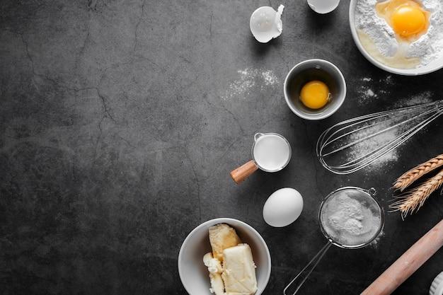 Vista dall'alto uova con burro e farina sul tavolo