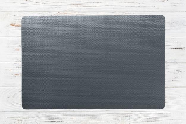 Vista superiore del tovagliolo di tavola nero vuoto per la cena sulla parete di legno con lo spazio della copia