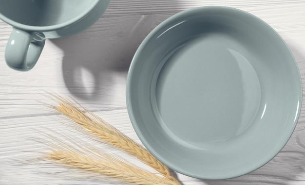 Vista superiore del piatto e della tazza di porcellana blu vuoti su fondo bianco di legno con le paglie di grano