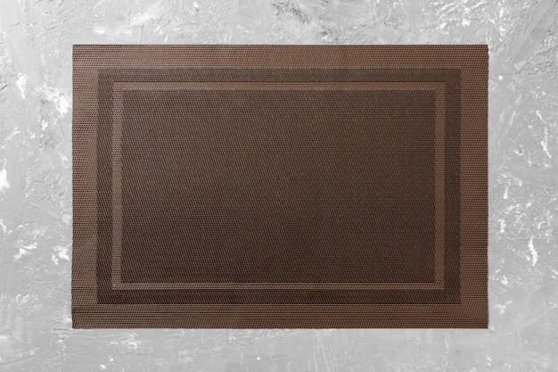 Vista superiore della tovaglia marrone vuota sul fondo del cemento con lo spazio della copia