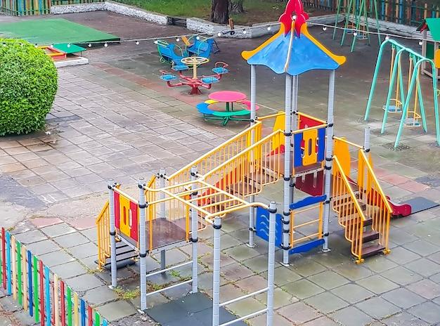 Vista dall'alto di un parco giochi per bambini colorato vuoto in un parco pubblico, altalene sicure, scivoli.