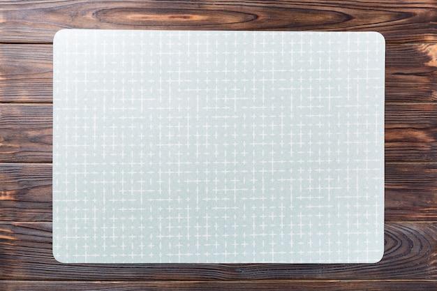 Vista dall'alto del tovagliolo da tavola verde vuoto per la cena su legno