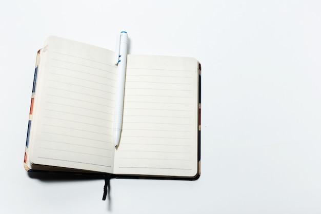 Vista dall'alto del taccuino e della penna vuoti, su sfondo bianco.