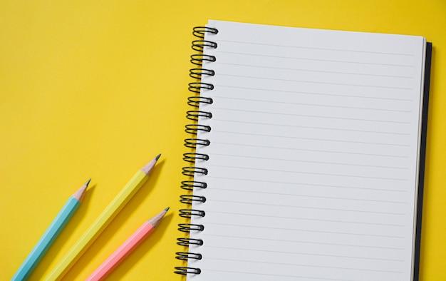Vista dall'alto di un quaderno a righe aperto vuoto con matite color pastello su sfondo giallo