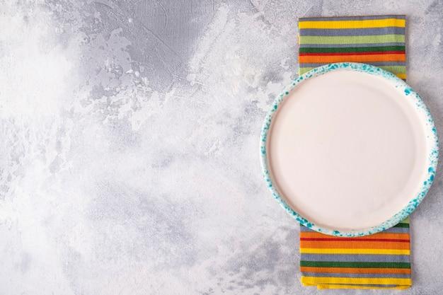Vista dall'alto del piatto di colore rotondo vuoto con tovagliolo su sfondo grigio. copia spazio