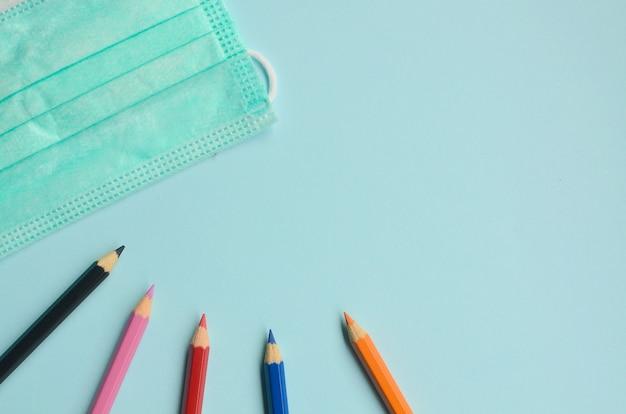 Vista dall'alto spazio vuoto con matite colorate e maschere su sfondo blu