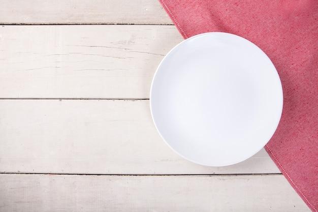 Vista dall'alto della piastra bianca vuota posto sulla tovaglia rossa e la tabella di legno bianca con spazio per la copia.