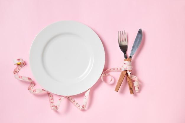 Vista dall'alto del piatto bianco vuoto con un coltello e forchetta avvolto in nastro di misurazione su sfondo rosa. concetto di dieta