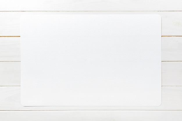 Vista superiore della tovaglia bianca vuota su fondo di legno con lo spazio della copia
