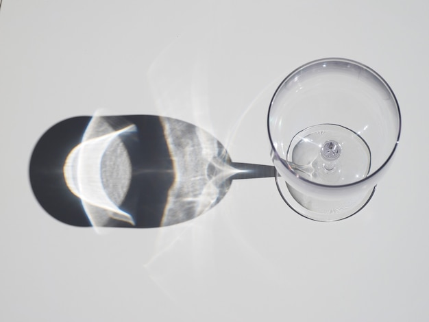Vista dall'alto del bicchiere di vino vuoto con ombra sul tavolo bianco durante la giornata di sole.