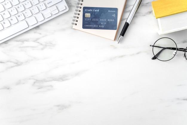 Vista dall'alto della stima e del pagamento della tassa di casa con calcolatrice e carta di credito da internet.