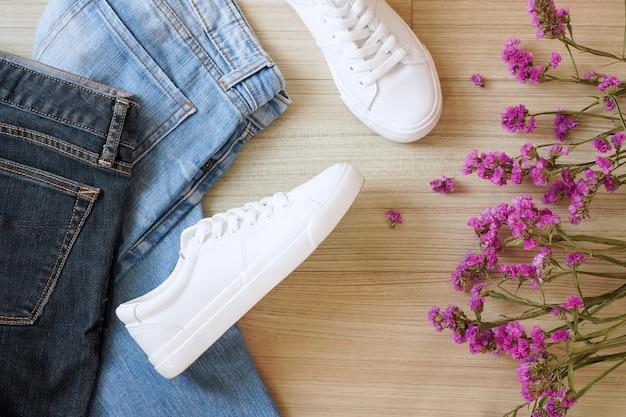 Vista dall'alto di jeans blu sbiaditi e scarpe da ginnastica bianche come moda streetwear da ragazza