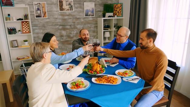 Vista dall'alto di bicchieri tintinnanti di famiglia con vino rosso mentre si fa un brindisi durante la cena con cibo delizioso.