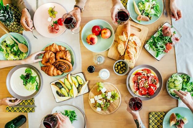 Vista dall'alto della festa della gente a tavola ricoperta di cibi e bevande con piatti, insalate, frutta, verdura, vino e salse