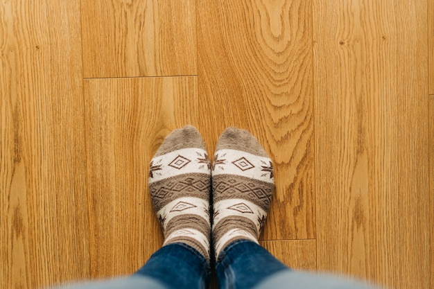 Vista dall'alto dei piedi in calzini caldi sul pavimento di legno