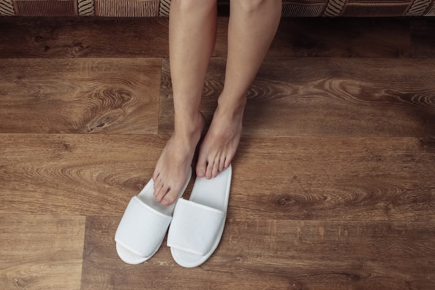 Vista dall'alto di gambe nude femminili con pantofole bianche su un pavimento di legno.