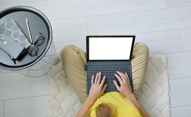 Vista superiore delle free lance femminili che si siedono sul pavimento vicino al sofà a casa e che lavorano con lo schermo in bianco del computer portatile