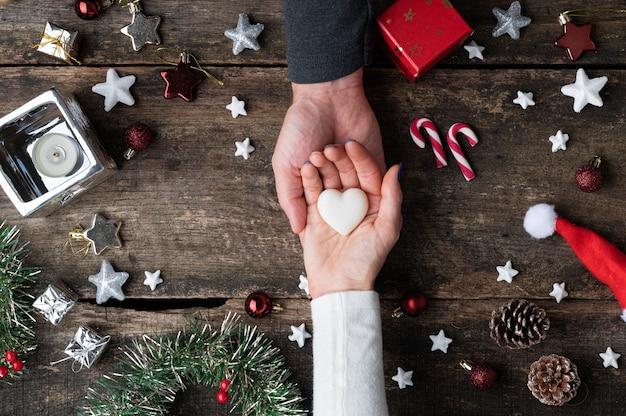 Vista superiore della mano femminile nel palmo della mano del partner che tiene il marmo fatto a forma di cuore nel centro della cornice natalizia.
