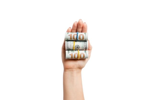 Vista dall'alto della mano femminile che tiene un sacco di banconote in dollari arrotolate su sfondo bianco isolato. concetto di povertà. concetto di credito.