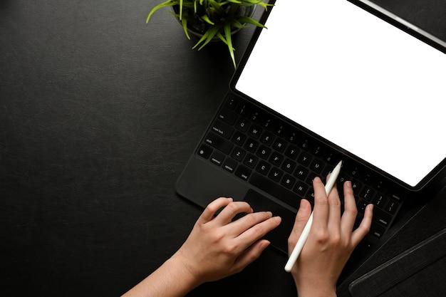 Vista superiore della mano femminile utilizzando la tavoletta digitale con tastiera e penna stilo sul tracciato di ritaglio dell'area di lavoro creativa scura