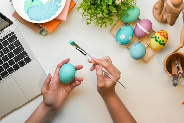 Vista superiore della mano femminile con il pennello che dipinge l'uovo di pasqua sull'area di lavoro con il laptop e gli strumenti