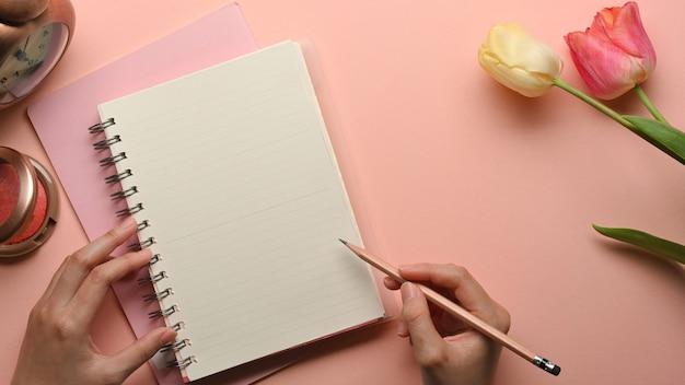 Vista superiore della mano femminile con la scrittura a matita sul taccuino in bianco sull'area di lavoro femminile rosa con il fiore