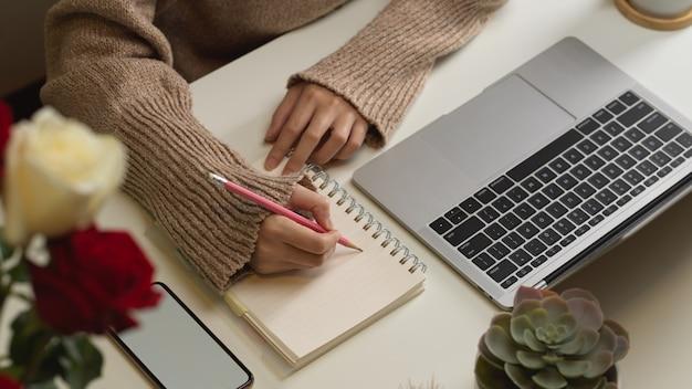 Vista superiore della mano femminile che scrive sul taccuino in bianco