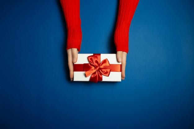 Vista dall'alto delle mani femminili che tengono confezione regalo con fiocco rosso su sfondo di blu fantasma di colore con spazio di copia. indossa un maglione di un lussureggiante colore lava.