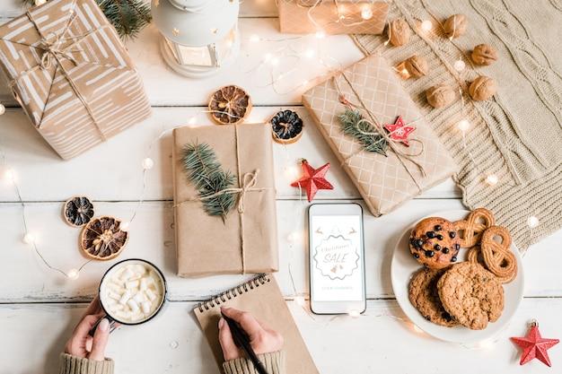 Vista dall'alto delle mani femminili con la penna sul taccuino che tiene la tazza con una bevanda calda tra regali confezionati, biscotti e decorazioni natalizie