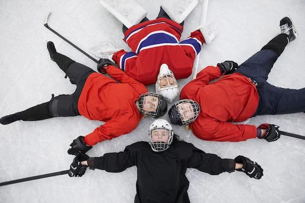 Vista dall'alto della squadra di hockey femminile sdraiato sul ghiaccio