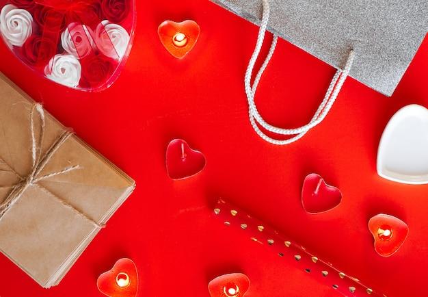 Vista dall'alto - sfondo rosso festivo per san valentino. il concetto di preparazione per le vacanze e regali di confezionamento.