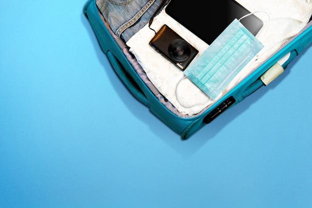 La vista dall'alto ha riempito la borsa dei bagagli con un tablet, una fotocamera e una maschera facciale su una superficie colorata. viaggiare nella nuova normalità