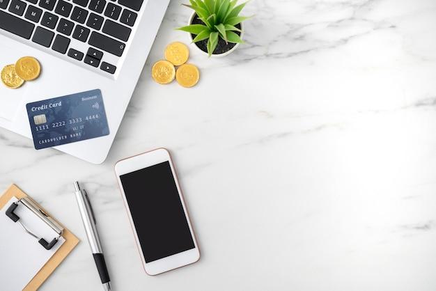 Vista dall'alto del concetto di piano finanziario con carta di credito, laptop, nota su sfondo bianco tavolo ufficio.