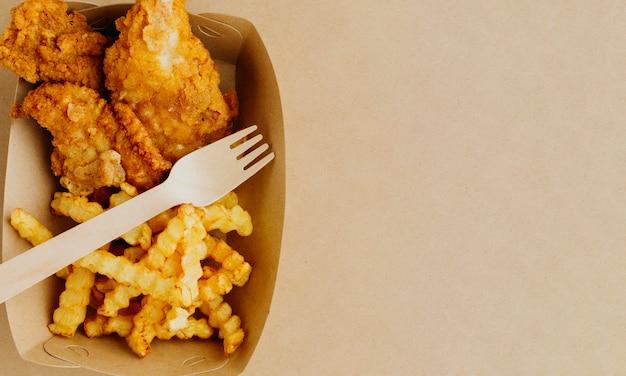Vista dall'alto di fish and chips con copia spazio e forchetta