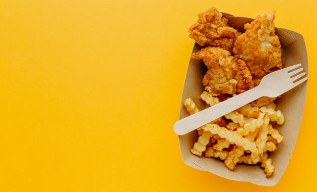 Vista dall'alto di fish and chips con forchetta e copia spazio