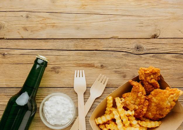 Vista dall'alto di fish and chips con forchette e bottiglia di barbabietola