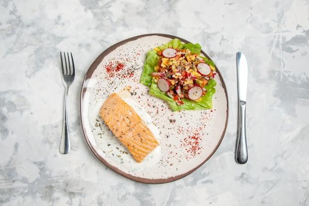 Vista dall'alto di farina di pesce e deliziosa insalata su un piatto e posate su una superficie bianca macchiata