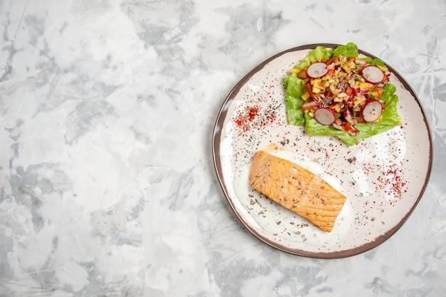 Vista dall'alto di farina di pesce e deliziosa insalata su un piatto sul lato sinistro sulla superficie bianca macchiata