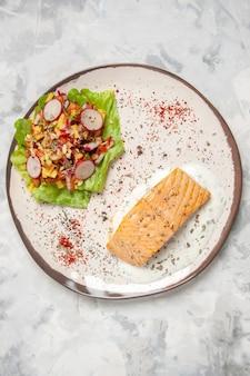 Vista dall'alto di farina di pesce e deliziosa insalata su un piatto sulla superficie bianca macchiata