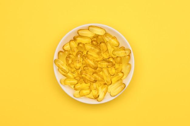 Vista dall'alto delle capsule di gel di olio di pesce in un piatto bianco su superficie gialla omega 3
