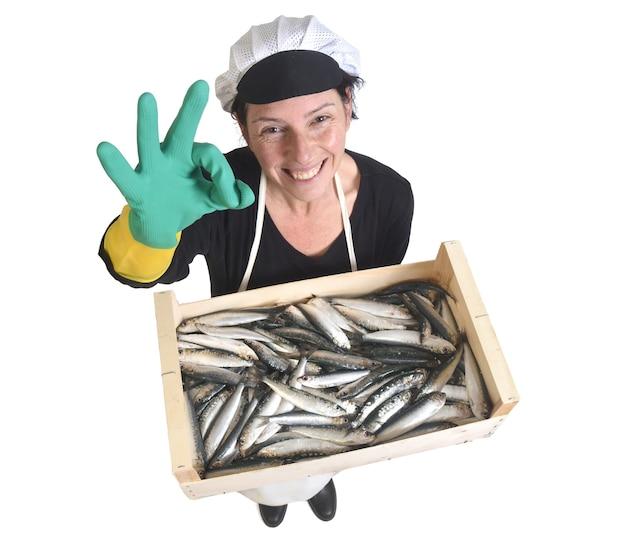 Vista dall'alto del pescivendolo che tiene una scatola di sardine e fa segno ok su sfondo bianco