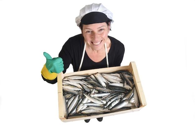 Vista dall'alto del pescivendolo che tiene una scatola di sardine pollici in su su sfondo bianco