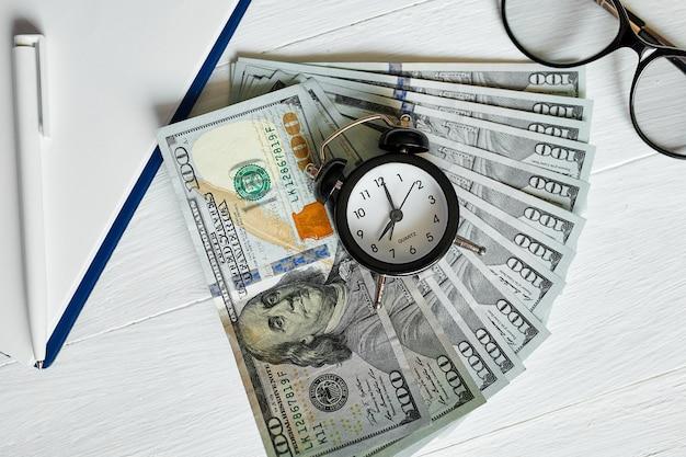 Vista dall'alto piatta di sveglia e denaro su sfondo di legno bianco, il tempo è denaro concept