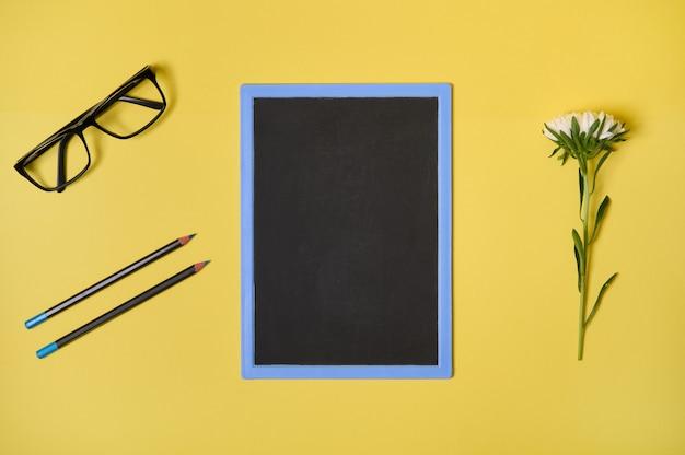 Vista dall'alto. disposizione piatta. lavagna pulita del fiore dell'aster di autunno con lo spazio della copia, occhiali e due matite, isolate su fondo giallo con spazio per testo. materiale scolastico per ufficio